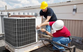 Two workers fixing air conditioning unit