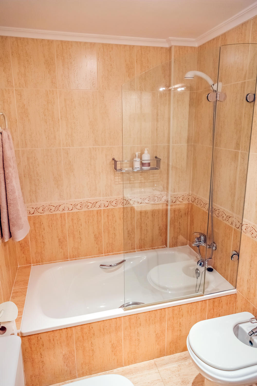 Bathroom with bathtub and shower screen
